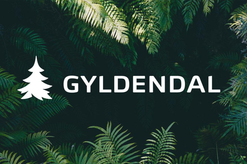 Gyldendals logo i hvitt på foto av planter