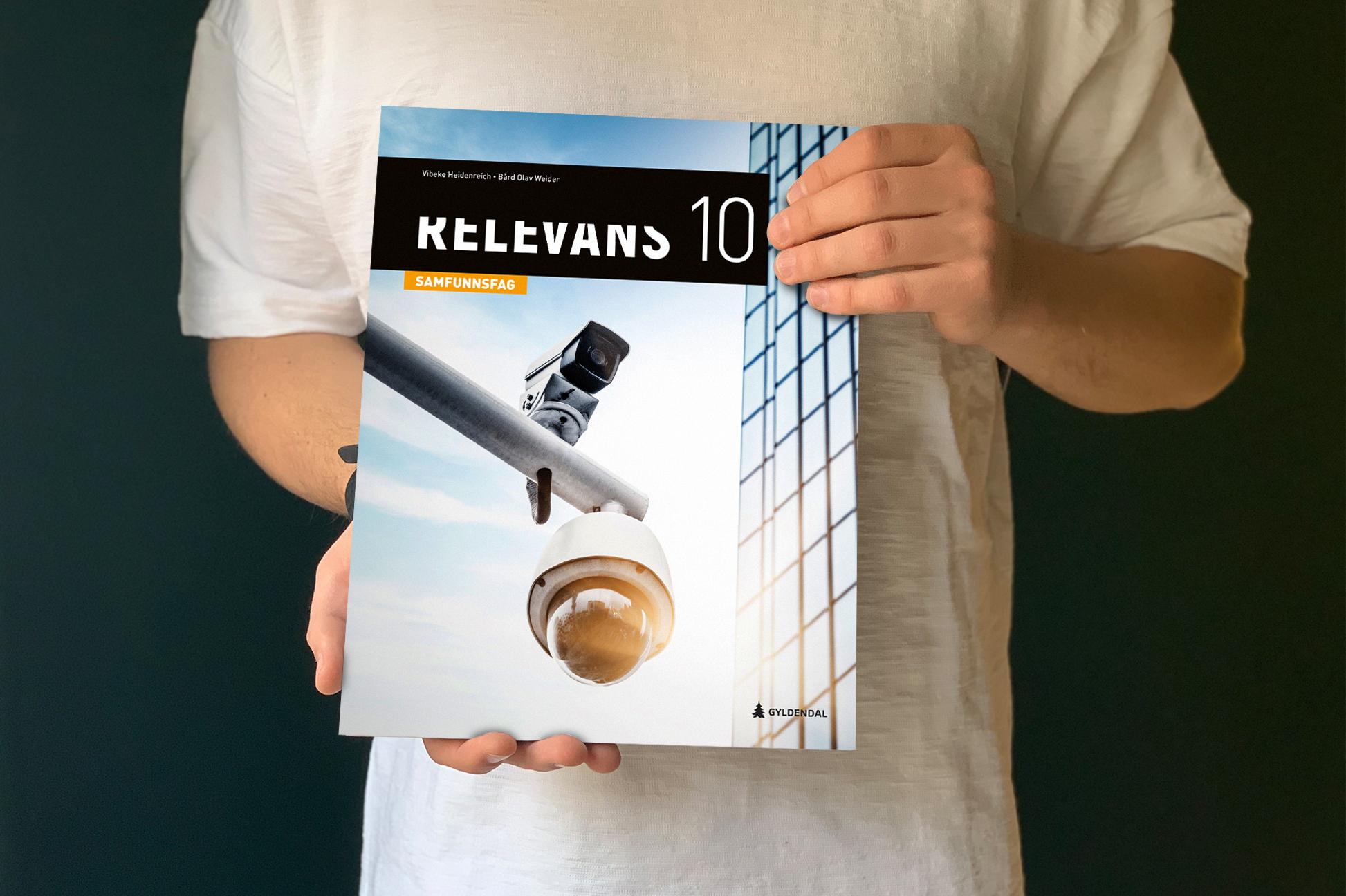 Mann i hvit t-shirt holder boken Relevans foran seg.