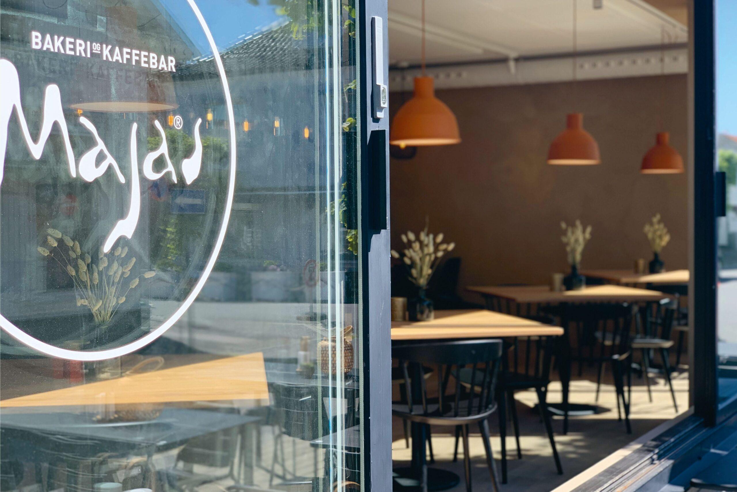 Stort vindu åpent fra utsiden av caféen. Lunt interiør med gulbeige toner og møbler i eik og sort.