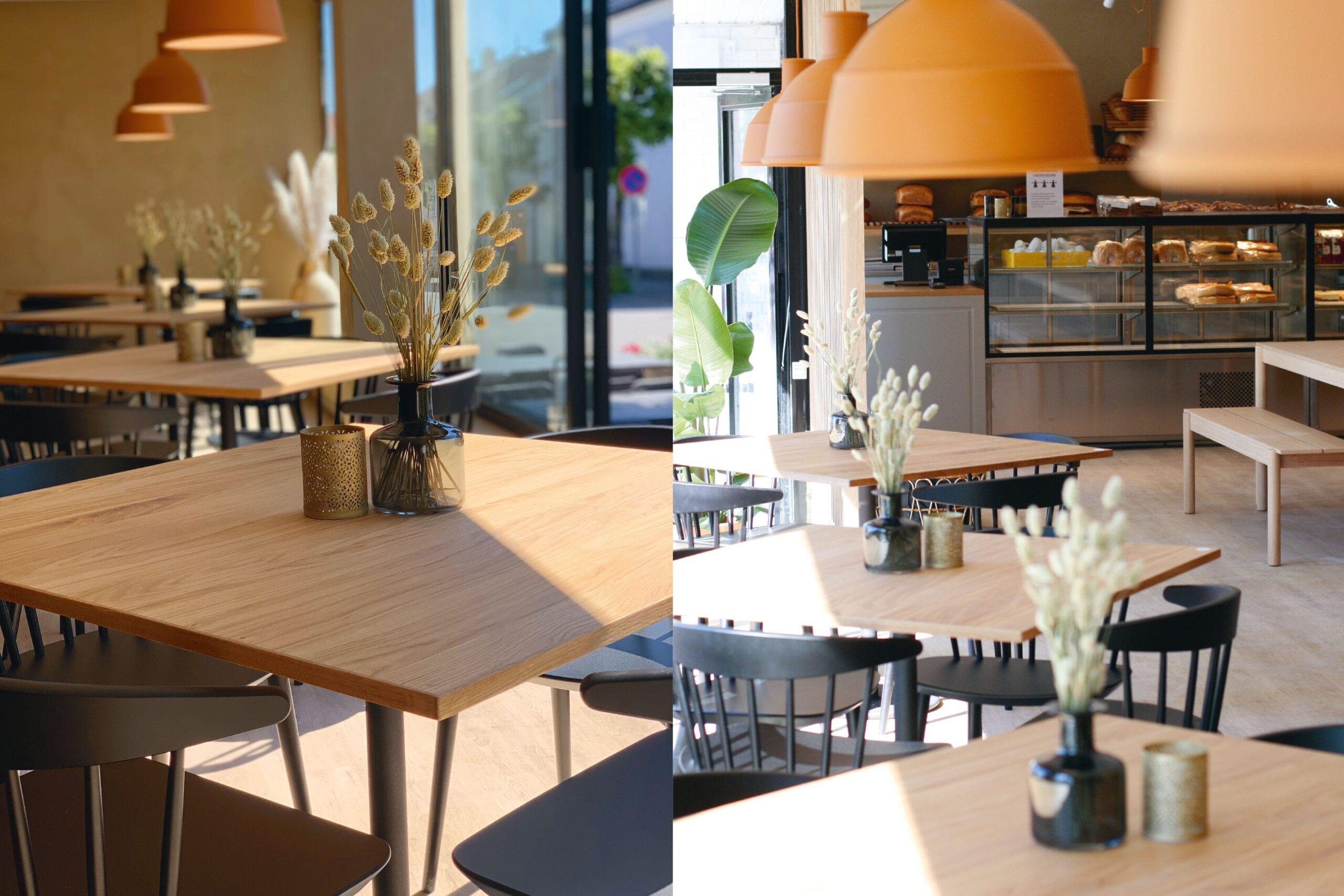 Vindussonen i caféen i sollys. Eikebord, sorte stoler og leirefargede lamper.