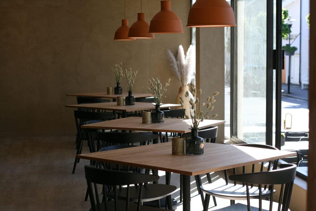 Cafébord langs vindu. Varmbeige vegger, eikebord, sorte stoler.