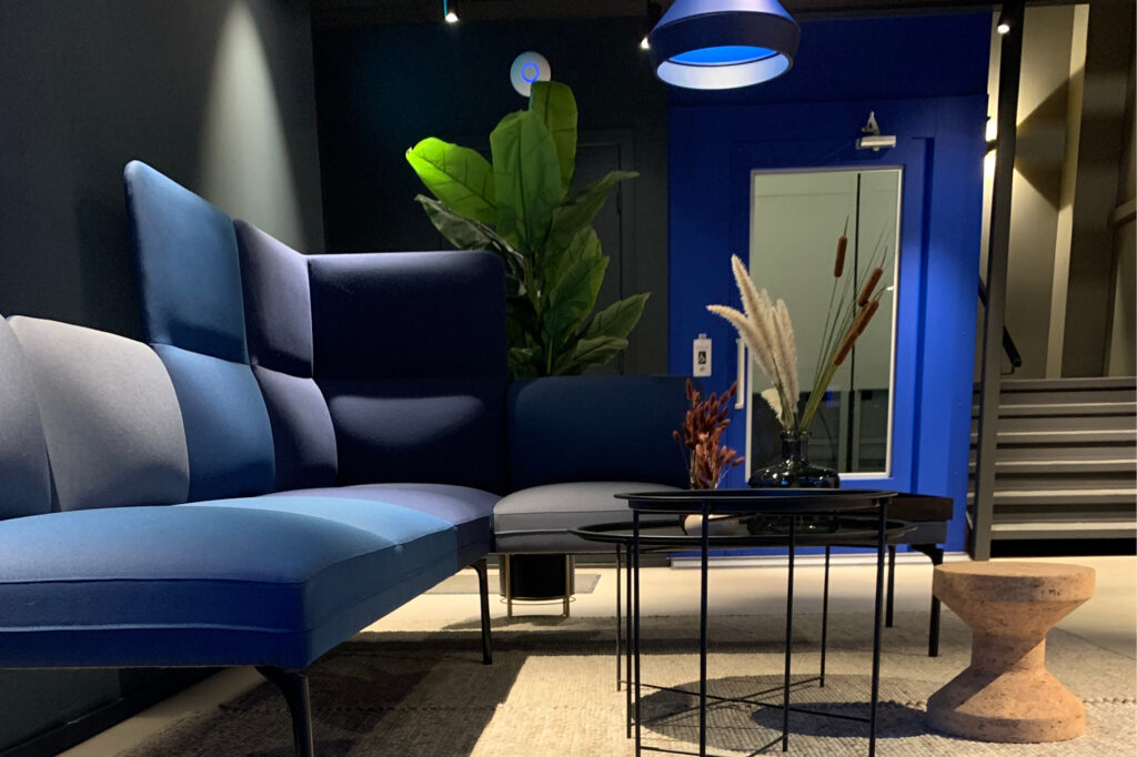 Lobby i kontorbygg med sofagruppe og knallblå heis