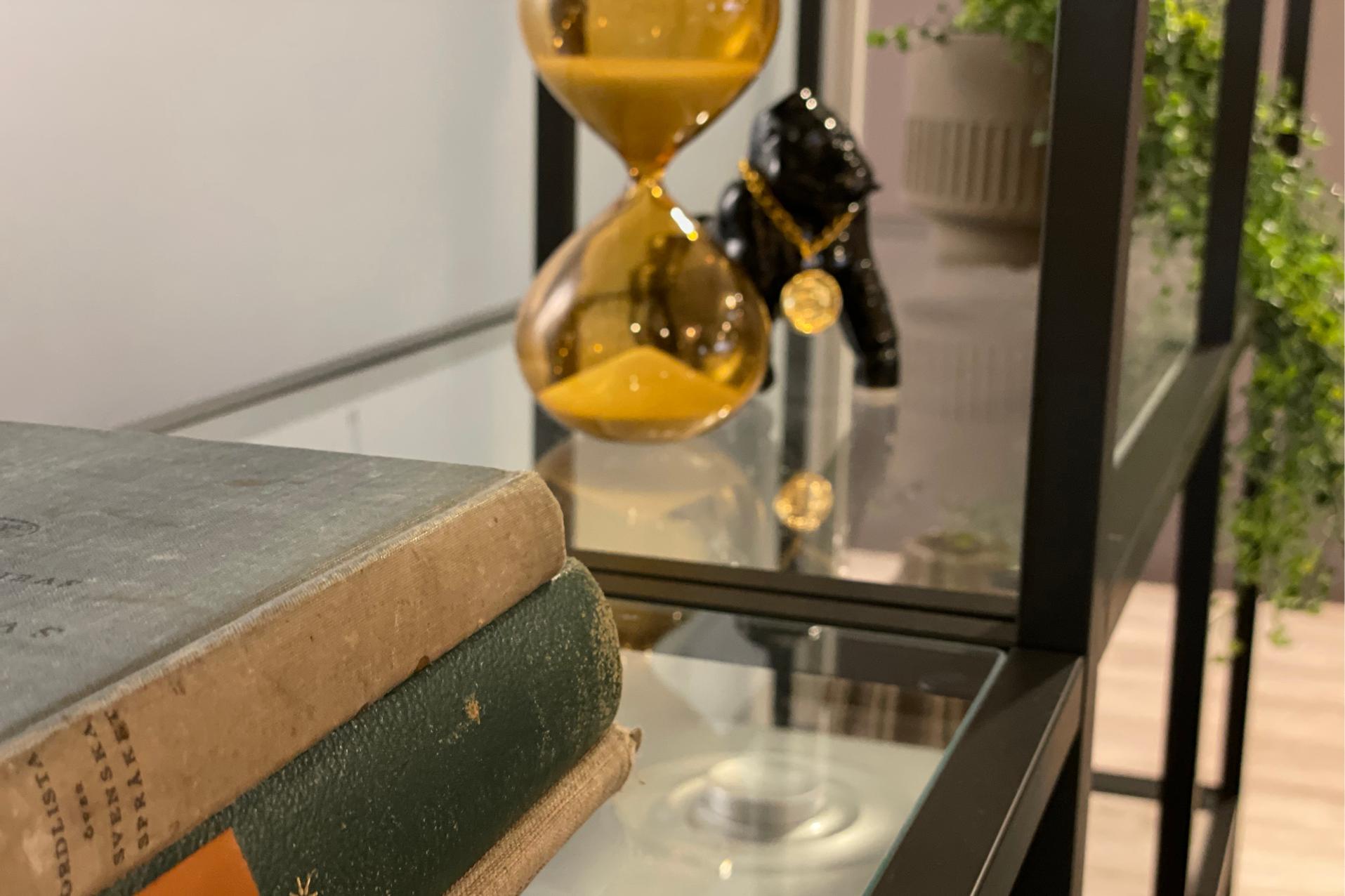 Bøker, timeglass, porselensgorilla og plante.